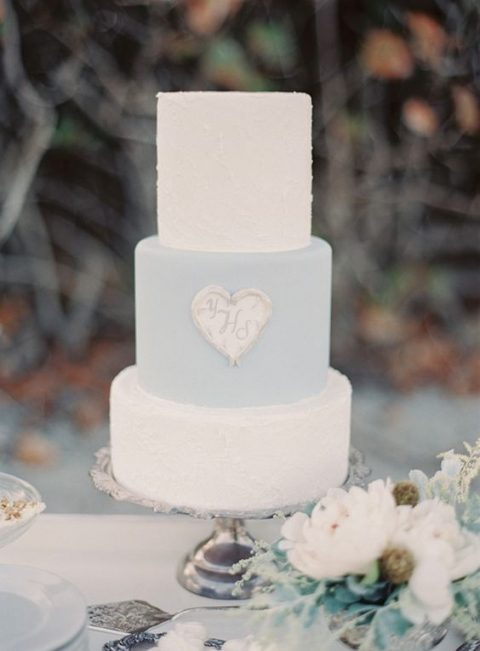 a white amd powder blue wedding cake with a heart with monograms