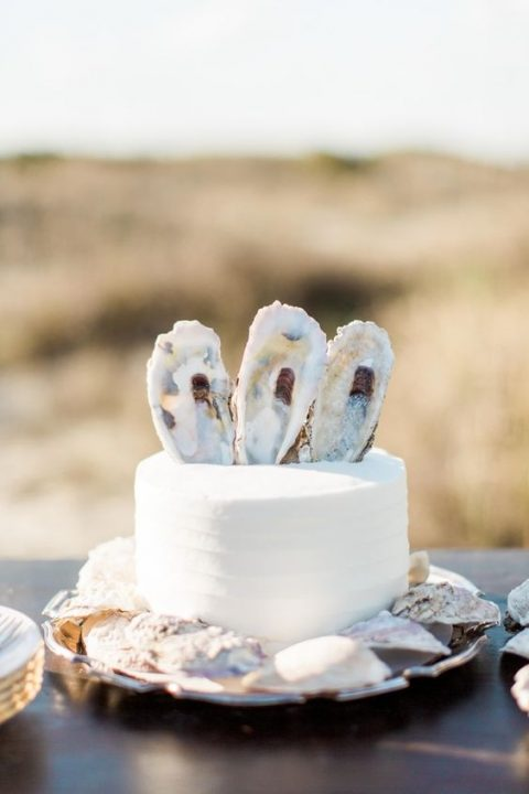 a white one-tier wedding cake with oyster shells on top