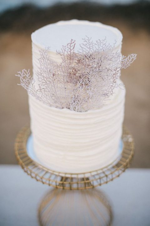 a white textural wedding cake with faux corals