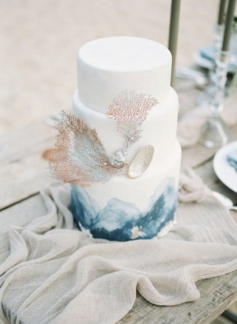 a white wedding cake with hand painting, faux corals and shells and pearls