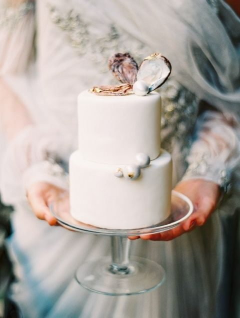 a white wedding cake with shells and pearls for an ocean wedding