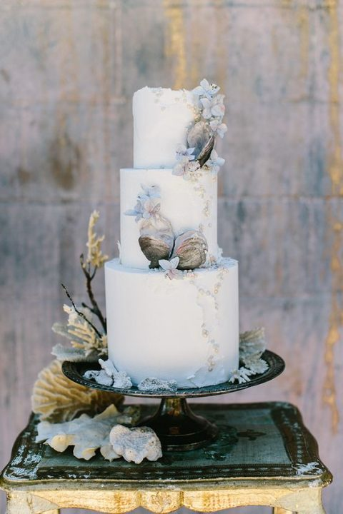 a white wedding cake with sugar shells and edible pearls