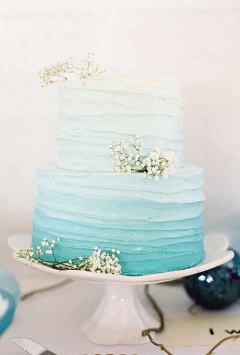 an ombre turquoise wedding cake with a texture and baby_s breath