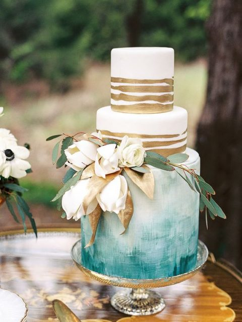 an ombre watercolor wedding cake with gold stripes and fresh blooms