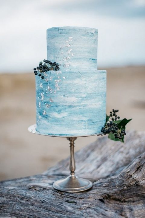 watercolor blue wedding cake with silver leaf and berries is a trendy solution