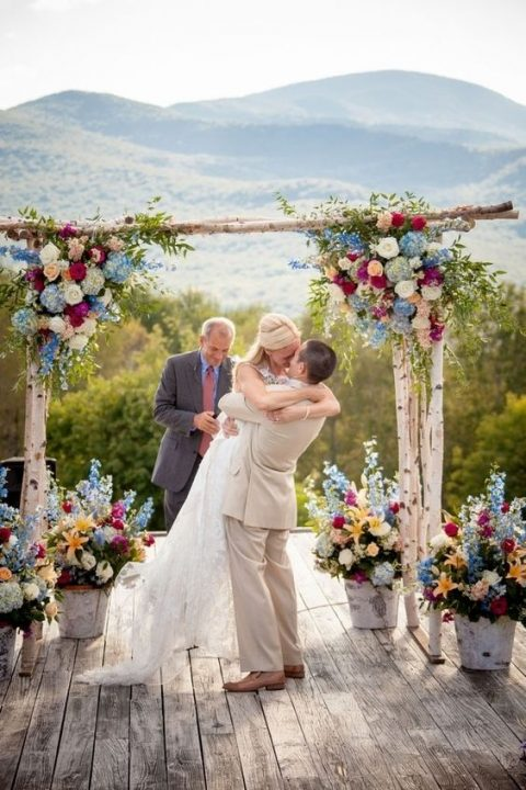 a bold rustic wedding arch with blue, white, green and fuchsia blooms and the same arrangement in buckets