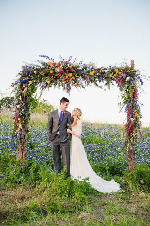 a bold wildflower-inspired wedding arch with red, yellow, blue and pink flowers and greenery