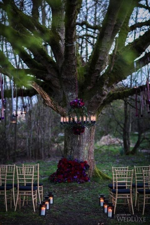 a candle chandelier and bold burgundy blooms for decorating a tree trunk