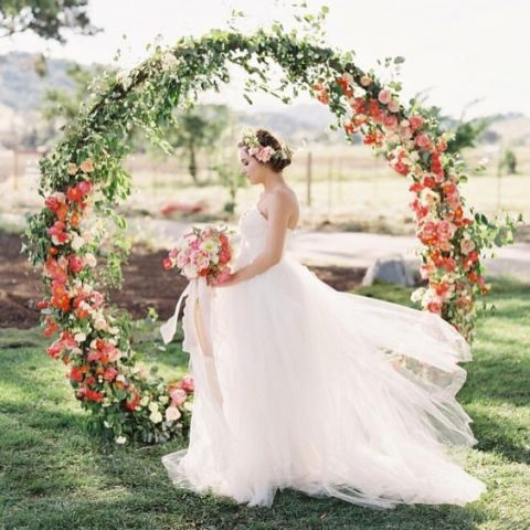 a giant circle wedding arch decorated with greenery and bold red blooms is a trendy solution