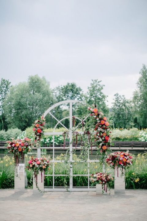 a gorgeous wedding altar of an old window and stands decorated with lush florals all over