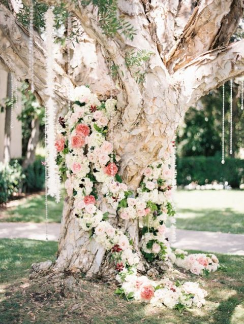 a large tree decorated with ivory and peachy blooms and hanging crystals