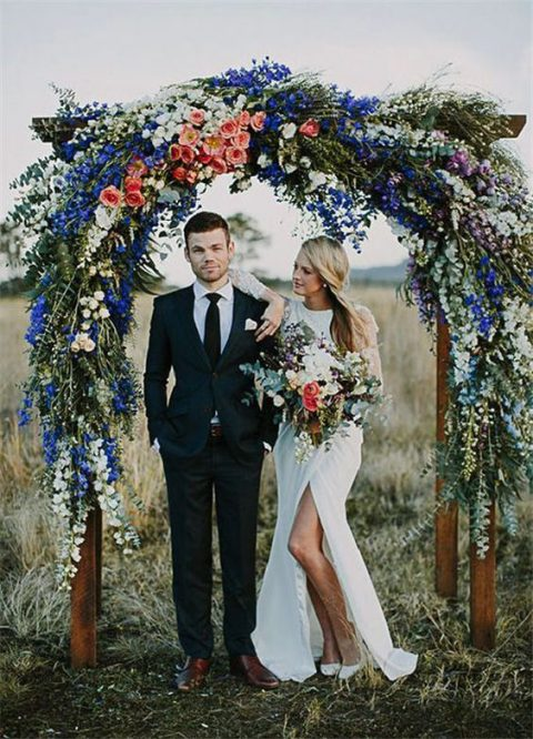 a lush floral wedding arch of peachy pink, blue and white flowers and greenery