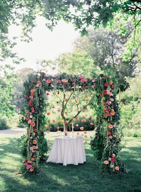 a lush greenery arch with red, pink and orange blooms and hanging flowers
