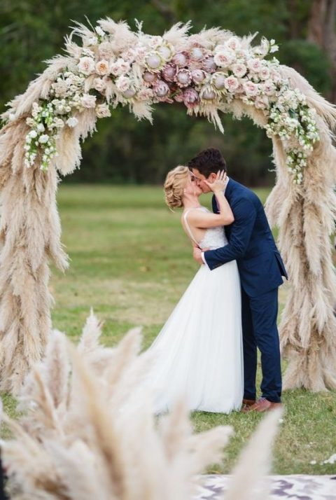 a lush pampas grass wedding arch decorated with king proteas, blush roses and white blooms