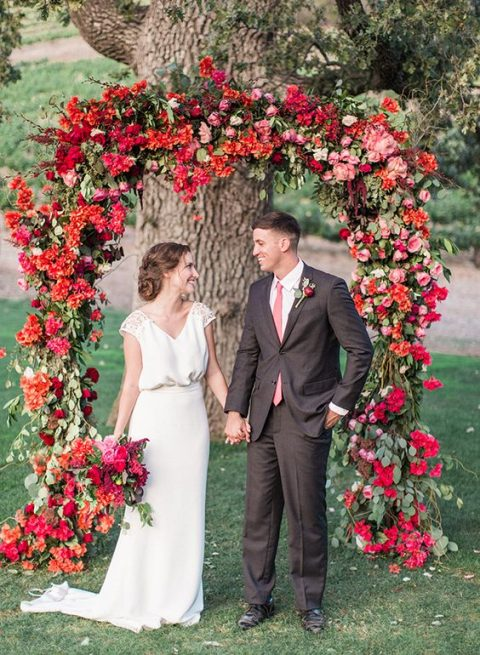 a lush red and fuchsia wedding arch with greenery