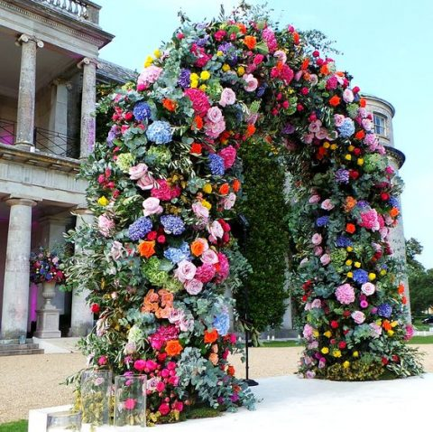 a lush wedding arch with blooms of pink, fuchsia, red, yellow, blue and purple flowers and greenery