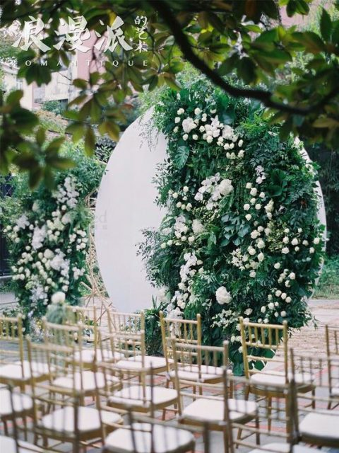 a modern wedding backdrop partly covered with lush greenery and white blooms