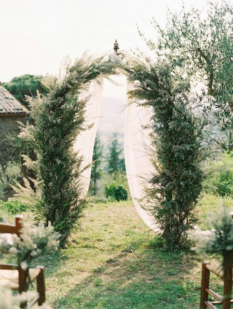a natural greenery wedding arch with white fabric