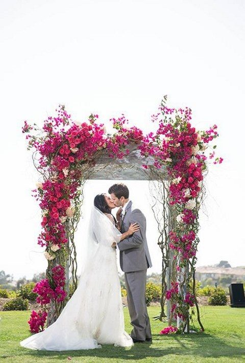a super bold fuchsia flower wedding arch for vivacious decor