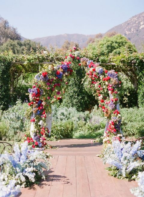 a super lush floral wedding arch with purple, blue, red and pink blooms plus greenery