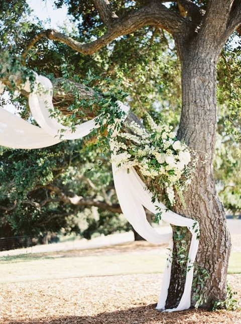 a tree covered with lush neutral florals, greenery and ethereal fabric