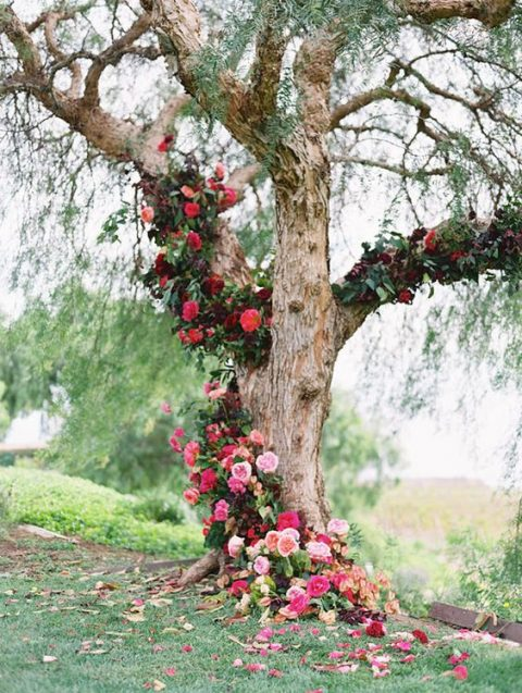 a tree decorated with bold red and fuchsia flowers for a wedding ceremony