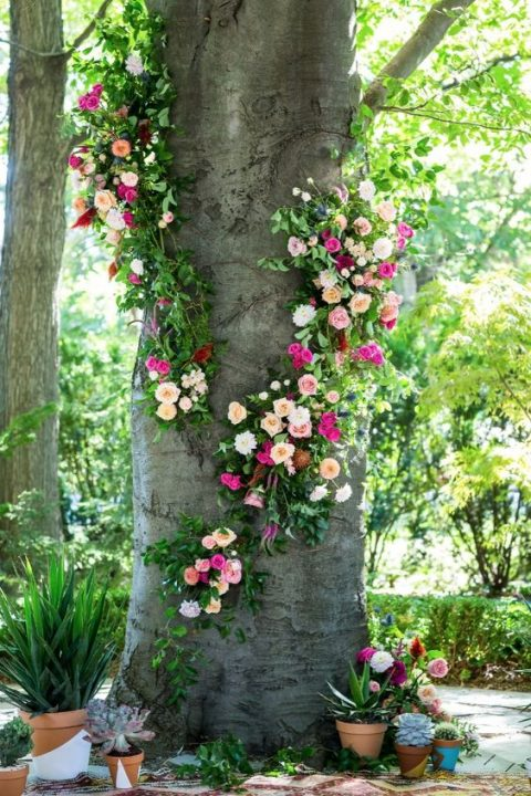 a tree decorated with bright pink and blush floral posies and greenery plus potted plants