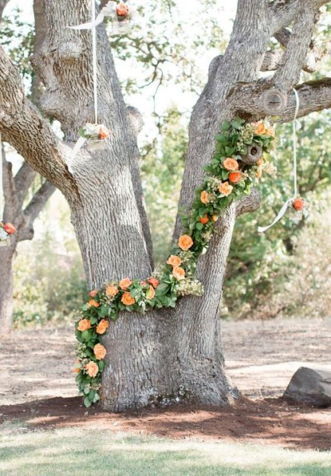 a tree decorated with lush greenery and orange blooms plus flowers in jars hanging from above