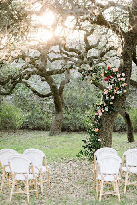 a tree trunk deocrated with blush and red blooms and lush greenery