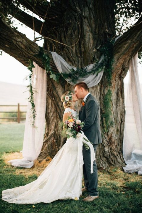 a tree with airy fabric and a greenery garland as a ceremony backdrop