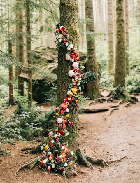 a tree wrapped with a bold floral garland in the shades of red and yellow