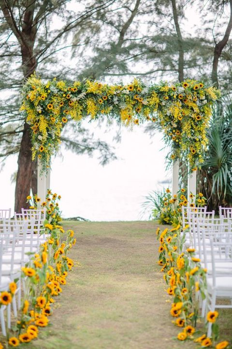 a wedding arch lushly decorated with sunflowers and greenery and the aisle lined with the same