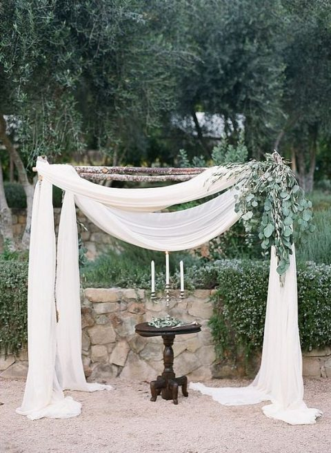 a wedding arch with ethereal white fabric and some eucalyptus