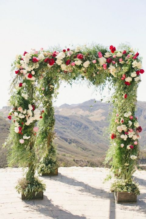 a wedding arch with white, red and pink blooms plus textural greenery