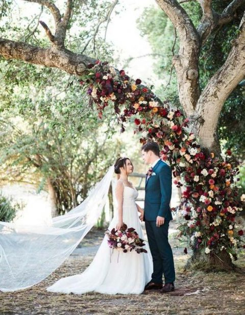 a wedding tree with a trunk fully decorated with burgundy, red, orange and other bold blooms