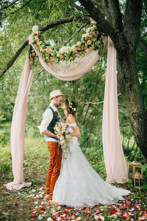 blush fabric, a crystal chandelier and a floral garland with peachy blooms