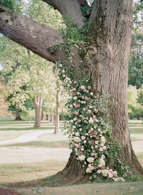 lush blush and ivory blooms and greenery on the tree trunk