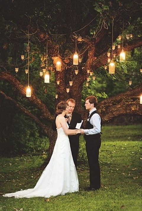 small lanterns and candle holders hanging form the tree