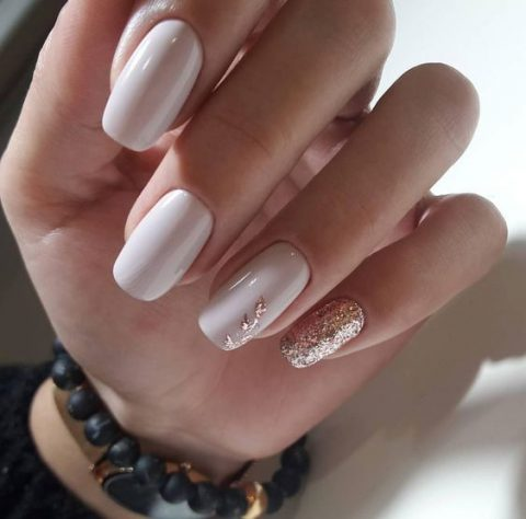 white nails with gold glitter touches and an accent nail