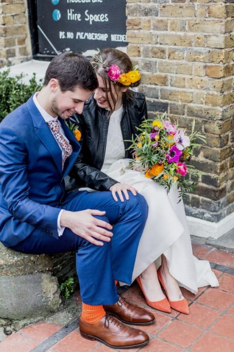 a black leahter jacket and orange suede shoes spruce up the wedding look