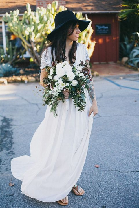 a boho bride showing off her tattoos and wearing a black hat