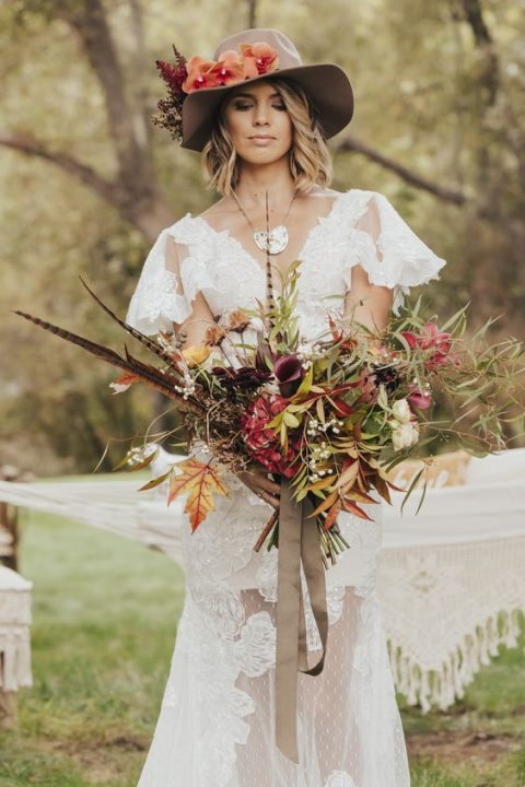 a boho bride wearing a flower embellished hat and a textural bouquet