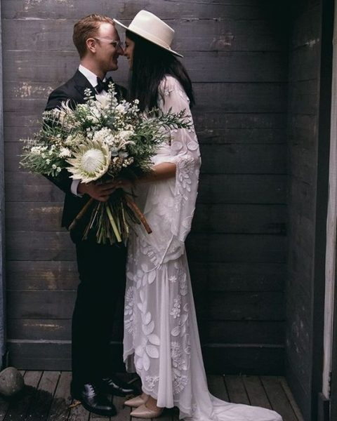 a boho bride wearing a lace dress with a train and a neutral hat
