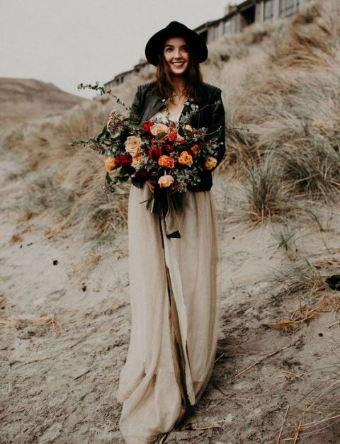 a boho chic bride in a neutral dress, a black leather jacket and a black hat