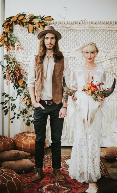 a boho groom in a leather vest and a brown hat