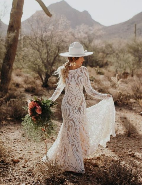 a boho lace wedding dress plus a white hat and statement earrings