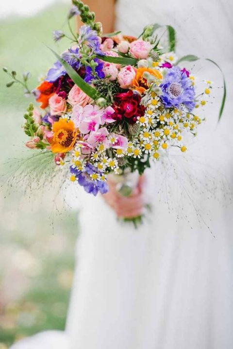 a bold bouquet with pink, purple, yellow, blush and red blooms plus daisies
