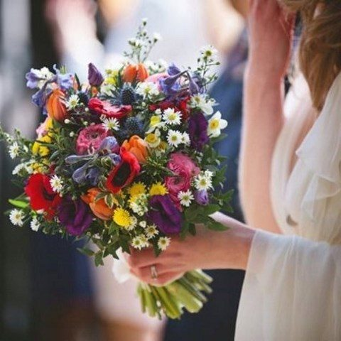 a bold bouquet with red, pink, blue, yellow and purple blooms and daisies