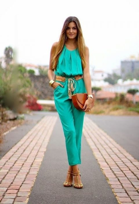 a bold green jumpsuit with a draped bodice and cropped pants, metallic shoes, a catchy clutch and a leather belt