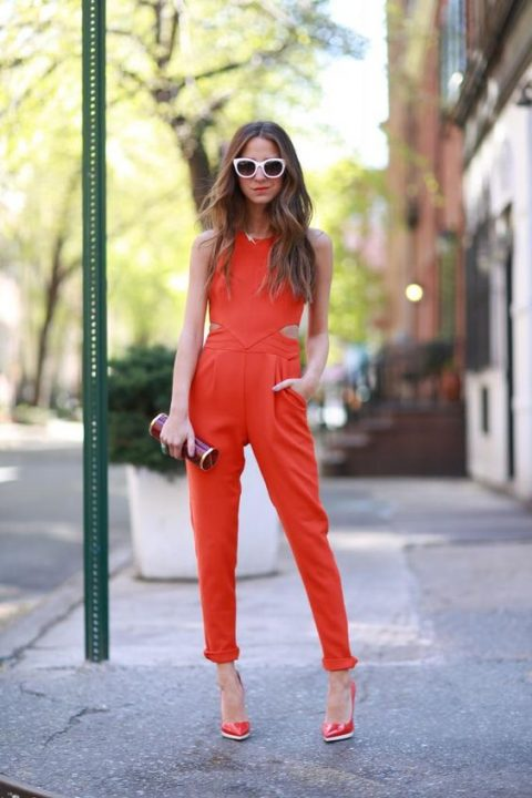 a bold orange jumpsuit with side cutouts, red shoes and a tube clutch